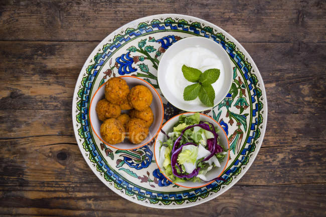 Falafel, salad, red and white cabbage, yogurt sauce with mint — Stock Photo
