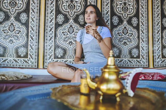 Марокко, портрет женщины с татуировкой хны на руке, пьющей чай — стоковое фото