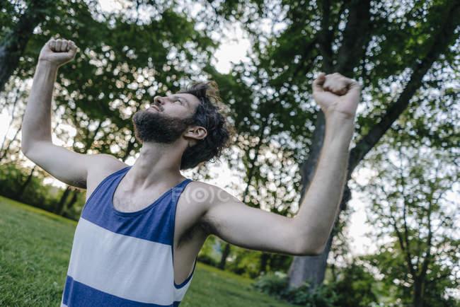 Man raising his arms in park — Fotografia de Stock