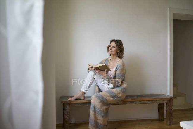 Mature woman sitting on wooden bench at home and reading book — Stock Photo