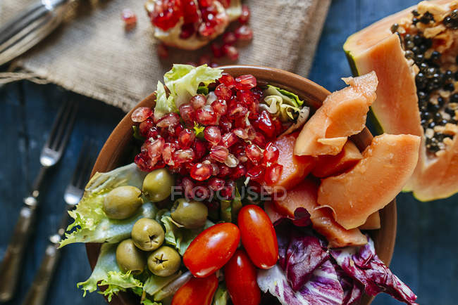 Close-up of papaya salad, pomegranate, lettuce, tomato, olives and endive in bowl — Stock Photo