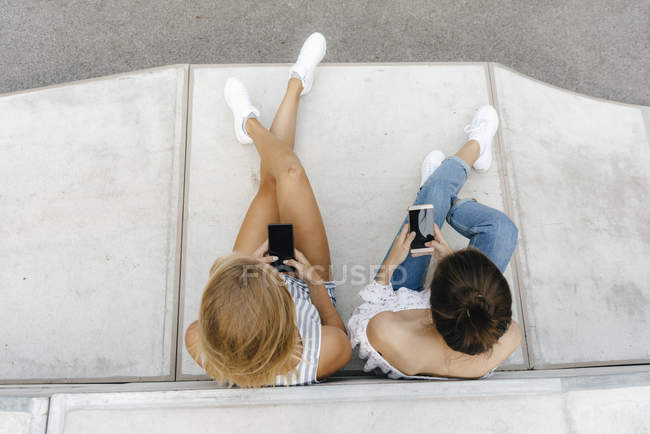 Due giovani donne che usano i telefoni cellulari nello skate park — Foto stock