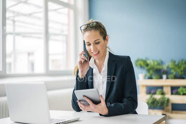 Empresária sentada na mesa, conversando ao telefone, olhando para tablet digital — Fotografia de Stock