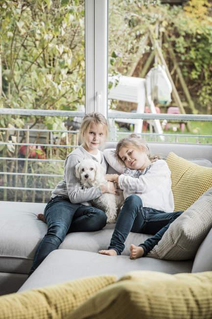 Портрет двох дівчат з собакою на дивані в вітальні — стокове фото
