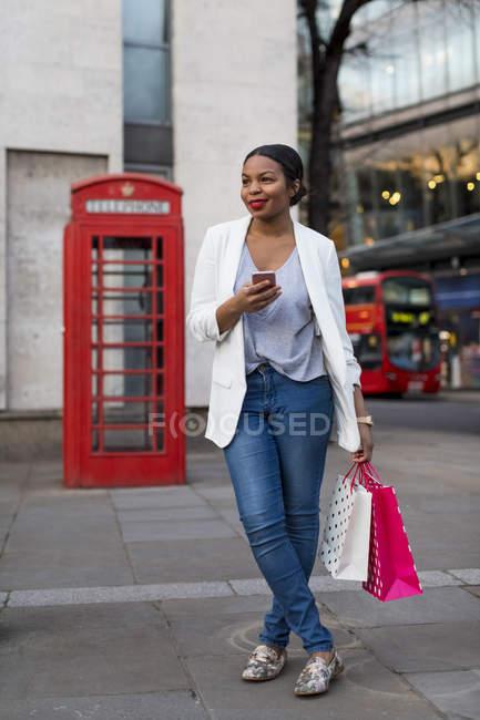 Regno Unito, Londra, donna sorridente con il cellulare che tiene borse della spesa in città — Foto stock