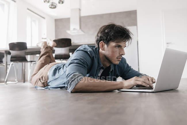 Uomo sdraiato sul pavimento in un loft e utilizzando il computer portatile — Foto stock