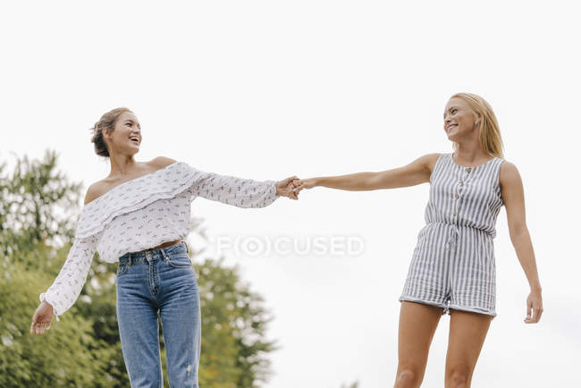 Two happy young girlfriends holding hands outdoors — Stock Photo