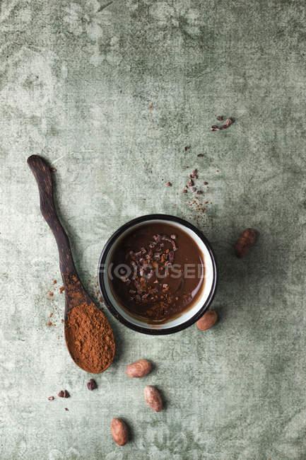 Tasse Schokoladenpudding mit Kakao, Kakaonibs und Kakaobohnen — Stockfoto