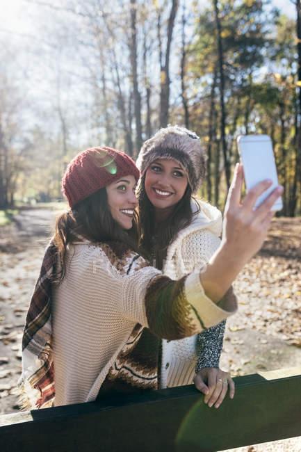 Duas mulheres bonitas tirando uma selfie em uma floresta outonal — Fotografia de Stock