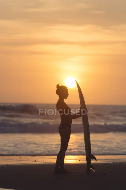 Indonesia, Bali, young woman with surfboard at sunset — Stock Photo