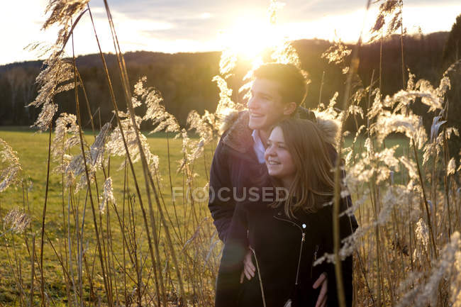Smiling young couple standing in reed against the sun — Stock Photo