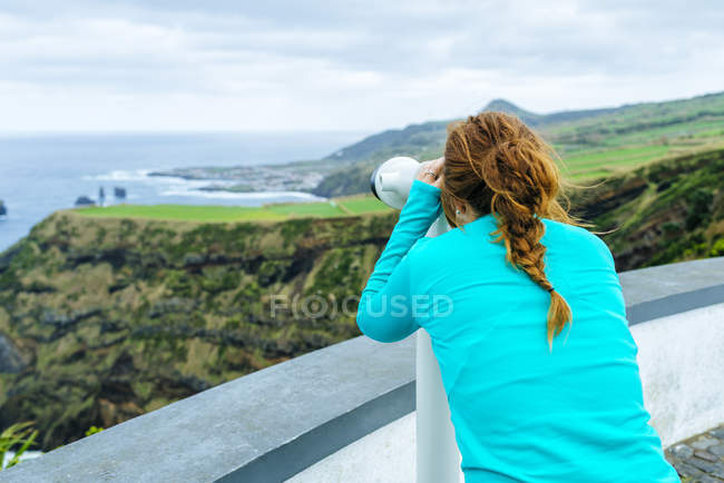 Azores, Sao Miguel, Woman looking through a tourist binoculars towards the sea — Stock Photo