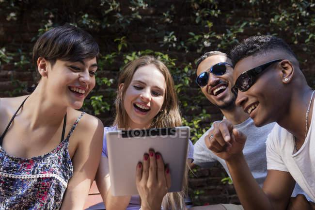 Счастливые друзья обмена таблетки на открытом воздухе — стоковое фото