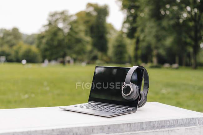 Ноутбук і навушники на стіні в парку — стокове фото