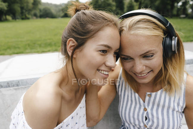 Two smiling young women sharing headphones outdoors — Stock Photo