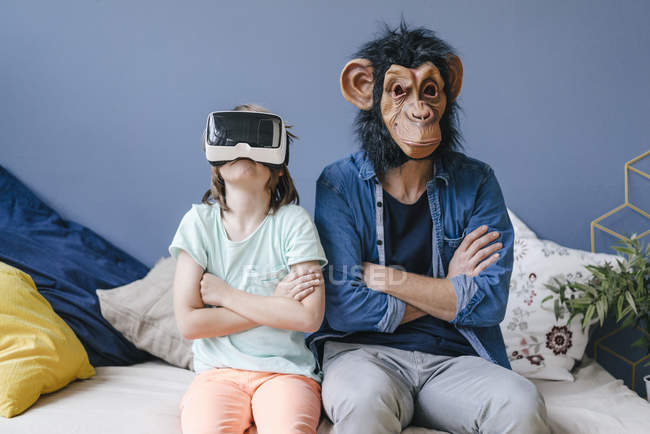 Отец в обезьяньей маске сидит рядом с сыном в виртуальных очках дома — стоковое фото