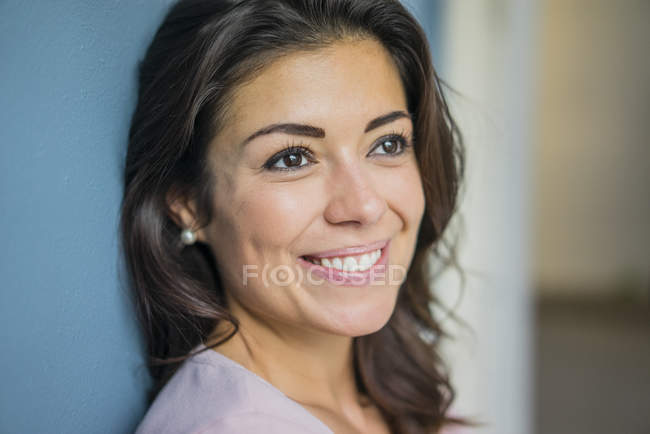 Portrait of happy young woman leaning against wall — Stock Photo