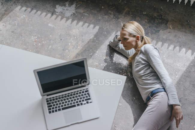 Mulher deitada no chão com laptop na mesa — Fotografia de Stock