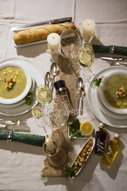 Garlic cream soup with croutons on festive laid table — Stock Photo