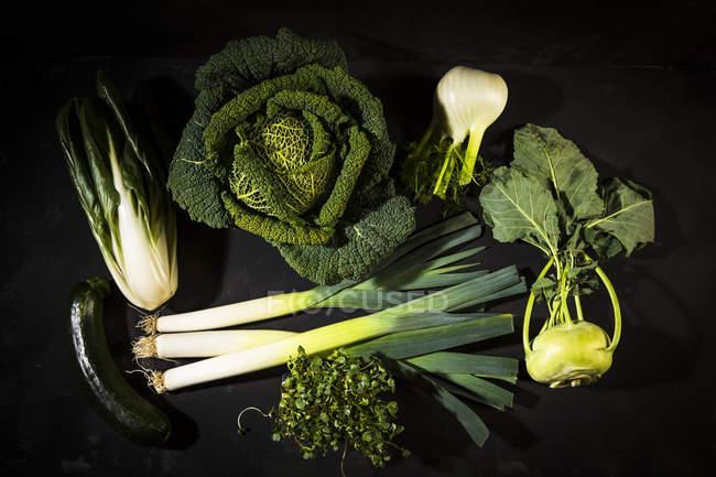 Legumes frescos espalhados na superfície preta — Fotografia de Stock