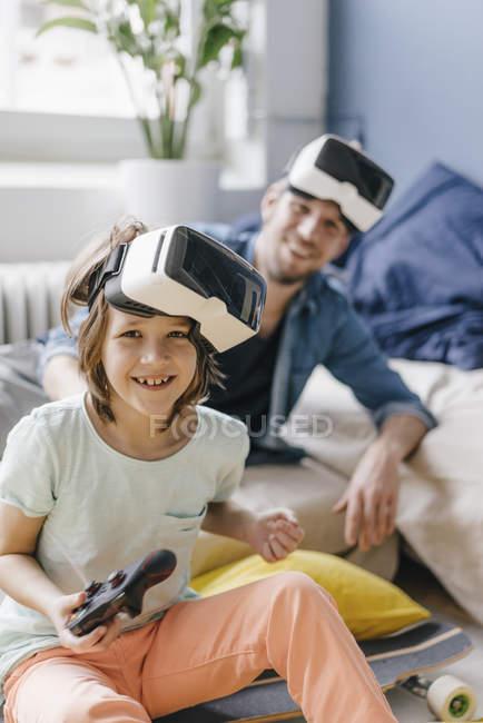 Портрет счастливого мальчика и отца в VR очках и в видеоигру дома — стоковое фото