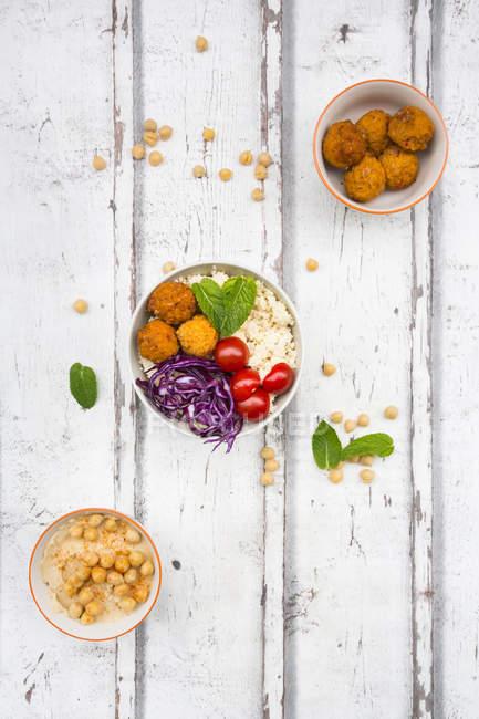 Süßkartoffelbällchen, Couscous, Hummus und Gemüse in Schüsseln — Stockfoto