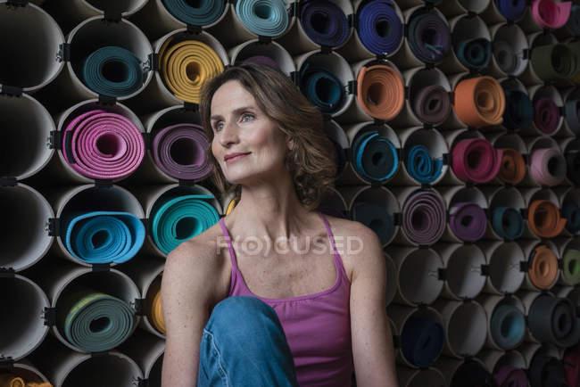 Lächelnde reife Frau vor einer Auswahl an Yogamatten — Stockfoto