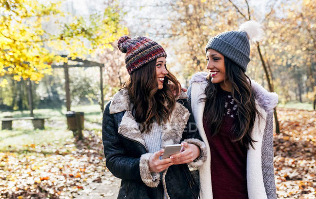 Two pretty women with cell phone smiling at each other in an autumnal forest — Stock Photo