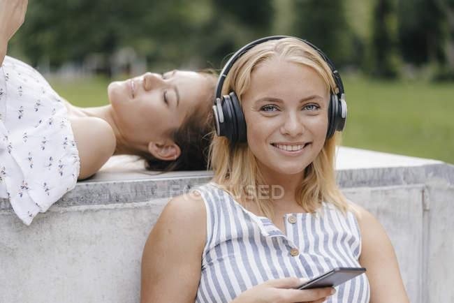 Retrato de mujer joven con teléfono celular y auriculares en skatepark - foto de stock