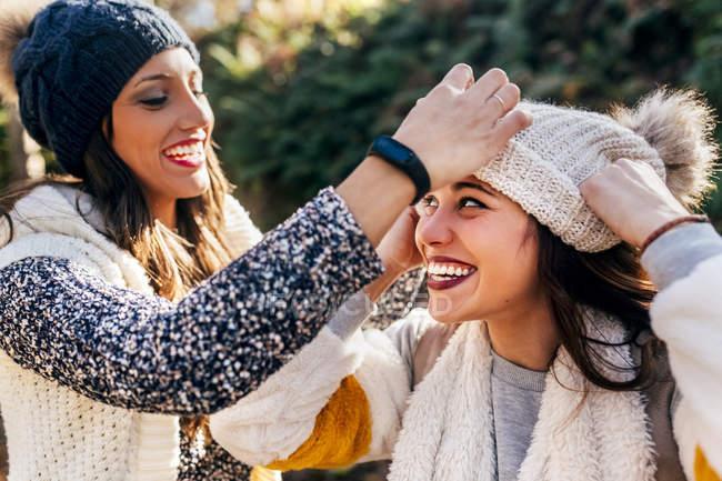Две симпатичные женщины веселятся с мокрыми шляпами — стоковое фото