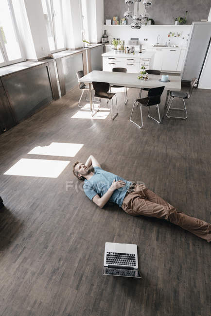 Pensive man lying on the floor in a loft — Stock Photo