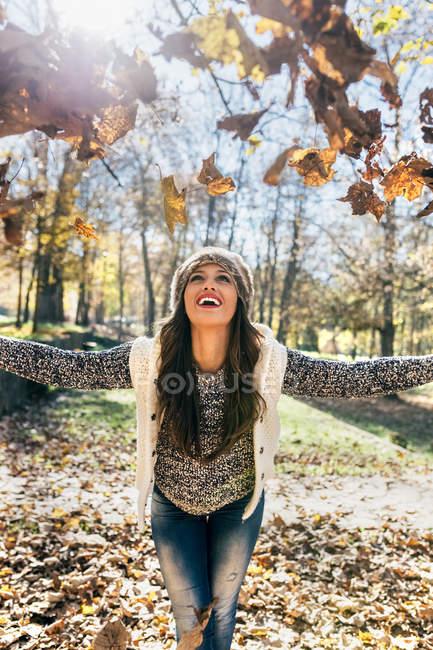 Красива щаслива жінка веселяться з листям в осінньому лісі — стокове фото