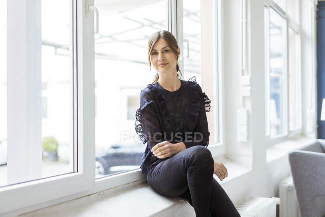 Porträt einer lächelnden Frau, die in einem hellen Raum am Fenster sitzt — Stockfoto