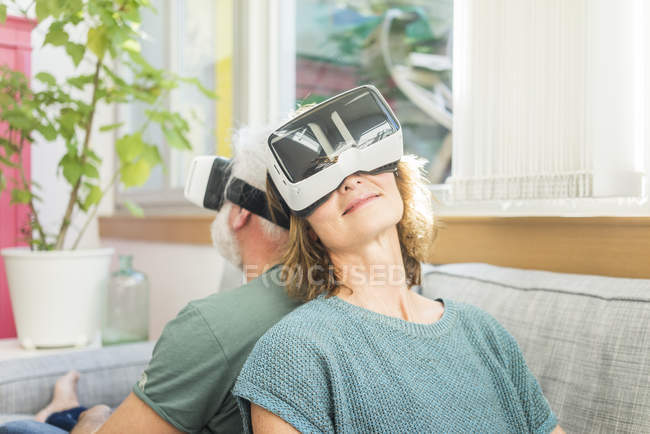 Mature couple sitting on couch at home and wearing VR glasses — Stock Photo