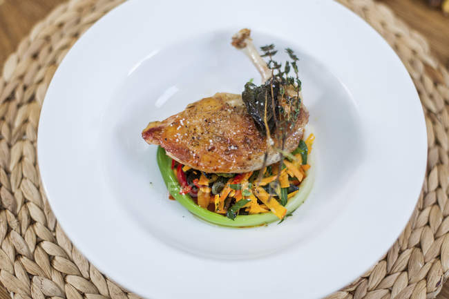 Chicken leg and vegetables on plate — Stock Photo