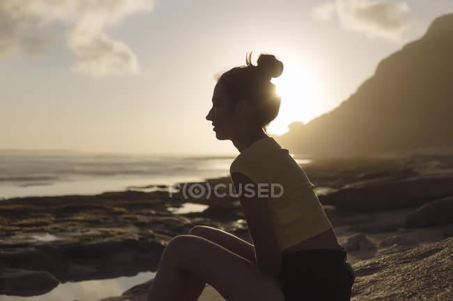 Індонезія, Балі, молода жінка, сидячи на пляжі на заході сонця — стокове фото