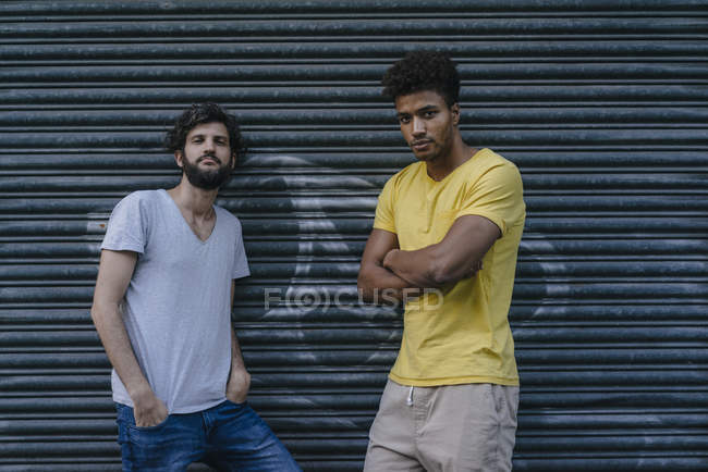Two multicultural friends standing at roller shutter in city — Stock Photo