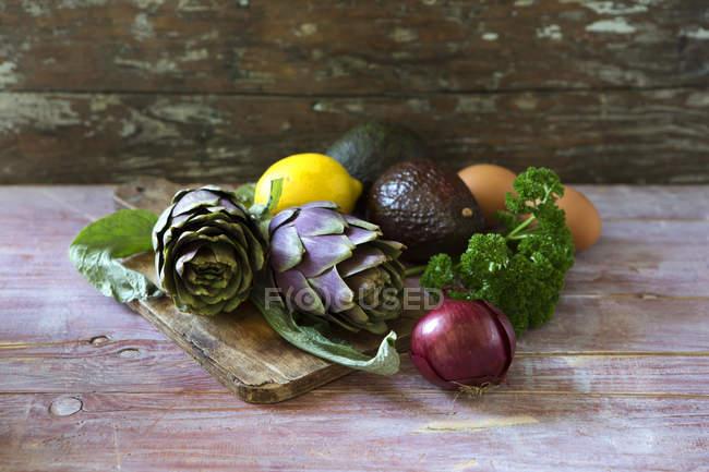 Fresh artichokes, onion, lemon, avocados and parsley on wooden board — Stock Photo