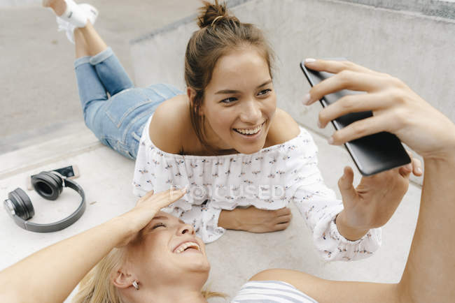 Two happy young women sharing cell phone in skate park — Stock Photo