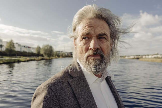 Portrait of serious senior man at lake — Stock Photo