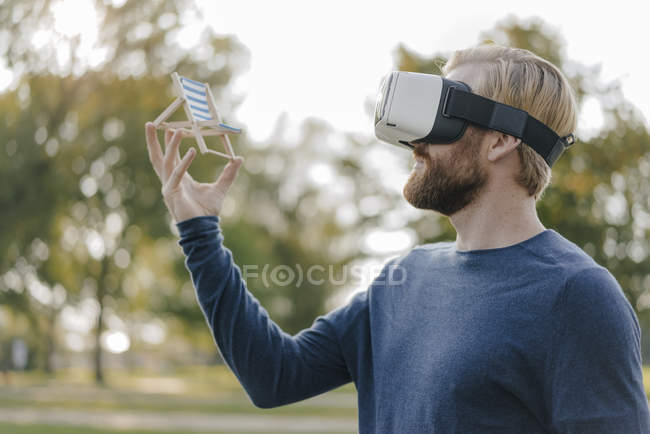 Man in autumnal park wearing Virtual Reality Glasses looking at miniature beach lounger — Stock Photo