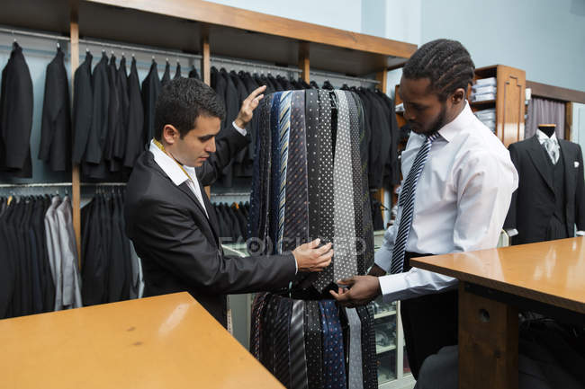 Tailor showing ties to client in tailor shop — стокове фото