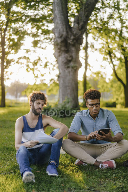Two multicultural friends sitting in park with mobile device and papers — Stock Photo