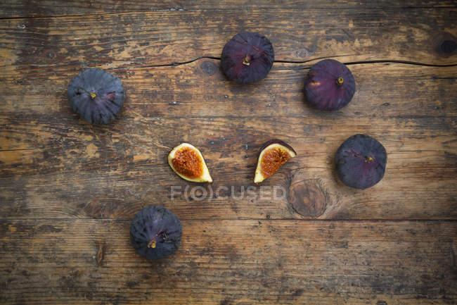 Figos frescos orgânicos com as fatias na tabela de madeira rústica — Fotografia de Stock