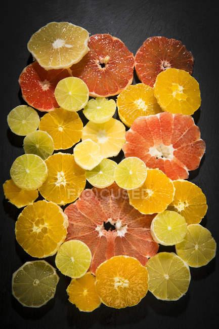 Fresh peeled and sliced citrus fruits on dark surface — Stock Photo