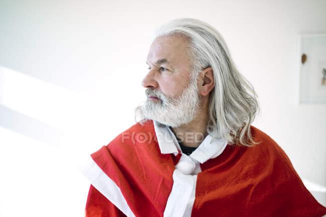 Бородатий зріла людина носіння Санта костюм і дивлячись sdeways — стокове фото