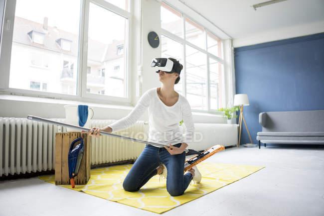 Mujer vital en casa con gafas VR mientras limpia el suelo - foto de stock
