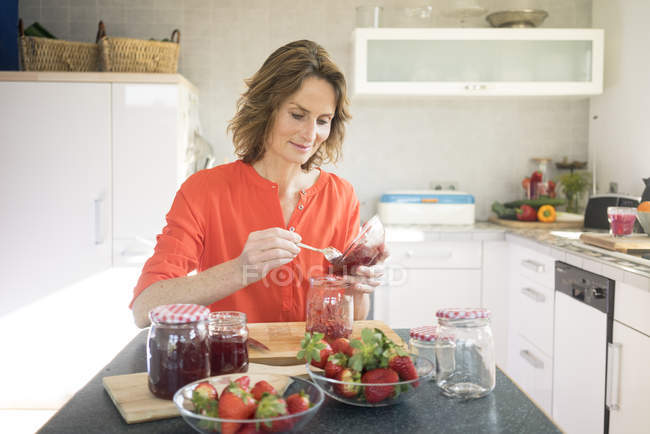 Portrait of woman making strawberry jam in kitchen at home — Stock Photo