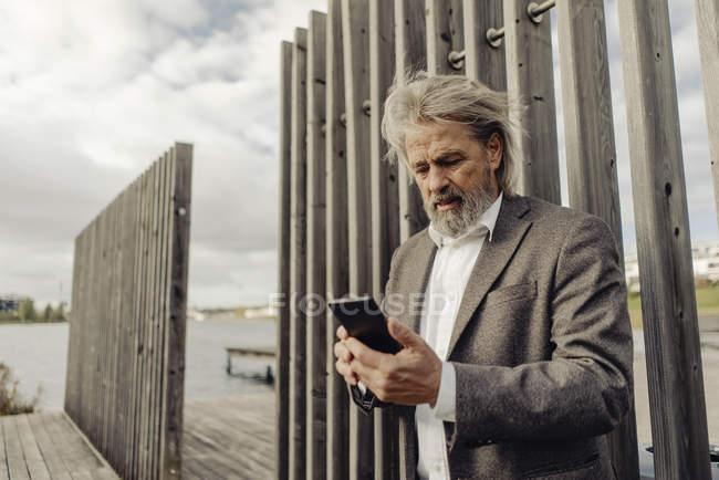 L'uomo anziano che usa il cellulare al lago — Foto stock