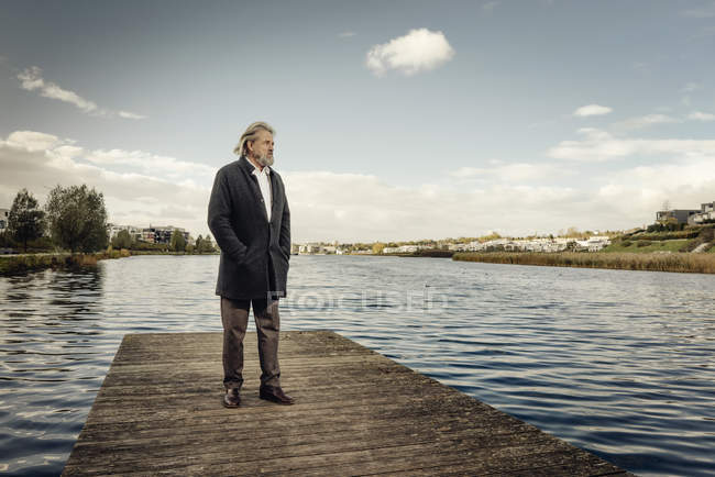 Senior man standing on jetty at lake — Stock Photo